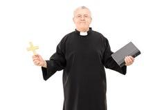 Reifes ehrwürdiges im schwarzen Umhang, der Bibel und ein Kreuz hält Stockbilder