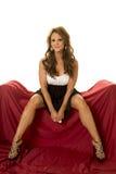 Reifes Frauenkleid sitzen auf rotem Blick der Beine auseinander Lizenzfreie Stockfotografie