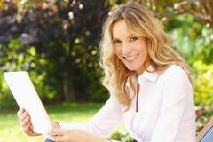 Reifes Frauenporträt mit digitaler Tablette Lizenzfreies Stockfoto