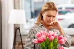 Reifes Fraugefühl empfindlich für Blumen beim Haben von Allergie lizenzfreie stockfotografie