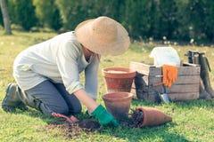 Reifes Mädchen, das in ihrem Hinterhof im Garten arbeitet Stockfoto