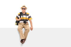 Reifes touristisches Sitzen auf einer leeren Anschlagtafel lizenzfreies stockfoto