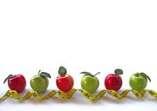 Reihe der Äpfel mit lockigem Bandmaß Lizenzfreies Stockbild
