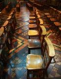 Reihe der alten hölzernen betenden Stühle Stockbild