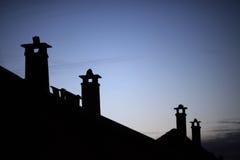 Reihe der alten Ziegelsteinkamine mit schwermütigem Abendhimmel Lizenzfreies Stockbild
