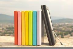 Reihe der bunten Bücher mit Ebuch Leser lizenzfreie stockfotografie