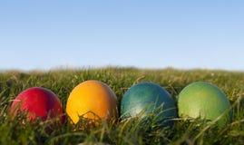 Reihe der farbigen Ostereier auf Gras mit blauem Himmel Lizenzfreies Stockfoto