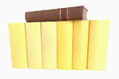 Reihe der gelben Bücher mit einem alten ledernen gebundenen Buch stockfotografie