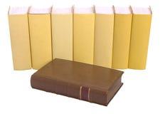 Reihe der gelben Bücher mit einem alten ledernen gebundenen Buch stockfoto