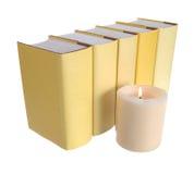 Reihe der gelben Bücher mit einer Kerze stockbilder