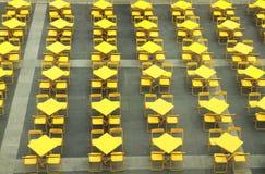 Reihe der gelben Tabellen und der Stühle lizenzfreie stockfotos