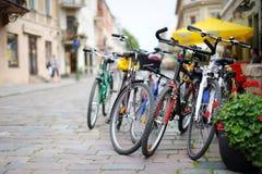 Reihe der geparkten bunten Fahrräder Stockbilder