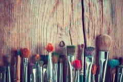 Reihe der Künstlermalerpinselnahaufnahme auf altem Holztisch, Retro- St. Lizenzfreie Stockfotos