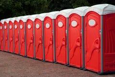 Reihe der roten beweglichen Toiletten Stockfotos
