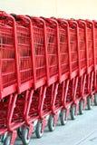 Reihe der roten Metalleinkaufenwagen Lizenzfreie Stockfotografie