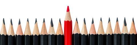 Reihe der schwarzen Bleistifte mit einem roten Bleistift in der Mitte Lizenzfreie Stockfotos