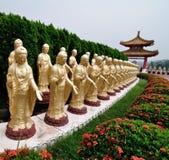 Reihe der Stellung der Buddha-Statue in einem Park Stockfotografie