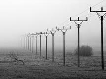 Reihe der Stromleitung Gondelstiele im Geheimnis-Nebel Stockfotos