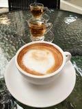 Reihe des Kaffees in der weißen Schale, Tee in den Transparenzschalen stockfoto