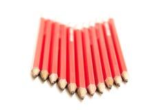 Reihe der roten Bleistifte in einer Pfeil-Form Stockbild