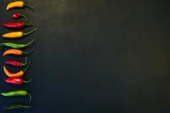 Reihe des Paprikas mit copyspace auf Schwarzem stockfoto