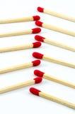 Reihe des roten Matchstick auf lokalisiertem Hintergrund Stockfotos
