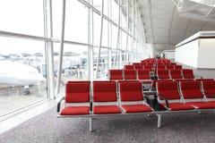 Reihe des roten Stuhls am Flughafen Stockbild