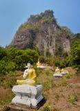 Reihe des Sitzens von Buddha-Statuen in Lumbini-Garten an der Unterseite von Stockbilder