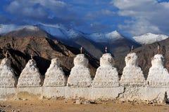 Reihe des weißen alten buddhistischen stupa auf dem Hintergrund der hohen braunen Berge von Tibet, ein klarer sonniger Sommeraben Stockbilder