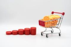 Reihe steigende Stapel der roten Münze nahe bei Warenkorb füllte wi lizenzfreies stockfoto