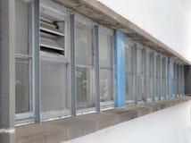 Reihe von alten Laufunten Bürofenstern Stockfoto