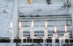 Reihe von brennenden Kerzen mit weißer Tempelwand als Hintergrund Lizenzfreie Stockfotos