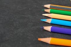 Reihe von bunten Bleistiften aus den schwarzen Grund Stockfotos