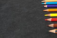 Reihe von bunten Bleistiften aus den schwarzen Grund Lizenzfreie Stockfotografie