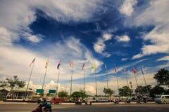 Reihe von bunten Flaggen in der Straße gegen blauen Himmel mit Wolken Stockbilder
