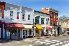 Reihe von bunten Shops entlang einem Ziegelstein-Bürgersteig lizenzfreies stockbild