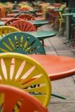 Reihe von bunten Tabellen und von Stühlen Stockbild