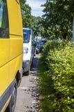 Reihe von den Autos, die auf der Straße nahe bei Hecke parken stockfotografie