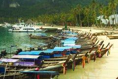 Reihe von den Booten des langen Schwanzes, die auf den Strand in Thailand warten Stockfoto