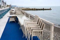 Reihe von den geflochtenen Stühlen entlang gestapelt auf einander und Cafétabellen Lizenzfreie Stockbilder