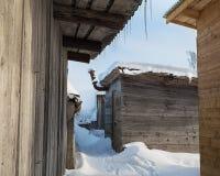 Reihe von den hölzernen Hallen bedeckt mit Schnee Eiszapfen, die von hängen Stockfotos