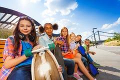 Reihe von den lächelnden Mädchen, die auf Holzbank sitzen Stockbilder