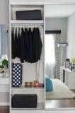 wandschrank mit der reihe des schwarzen kleides h ngend am kleiderb gel stockfoto bild von. Black Bedroom Furniture Sets. Home Design Ideas