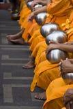 Reihe von den sitzenden Mönchen, die Almosen empfangen stockfoto