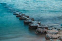 Reihe von den Steinen, die auf das Meer treten Lizenzfreie Stockbilder
