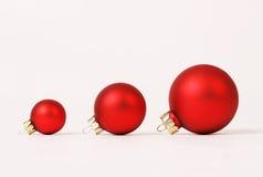 Reihe von drei roten matten verschiedenen Größenweihnachtsbällen Stockfotografie
