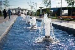 Reihe von einigen Wasserbrunnenabschluß oben im Park mit Sprühtropfenjets Hintergrund stockfotografie