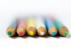 Reihe von farbigen Zeichenstiften oder von Bleistiften auf weißem Hintergrund, Makro, Nahaufnahme, defocused, abstrakt, Bildung Stockfoto