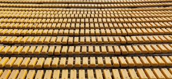 Reihe von gelben hölzernen Sitzen auf einem Zuschauerhaupttribünenfoto Stockfotografie