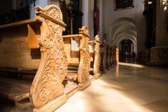 Reihe von geschnitzten Holzbanken in St- Michaelbasilika, Mondsee, Österreich Stockbild